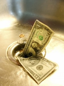 Picture of money going down a drain of a kitchen sink