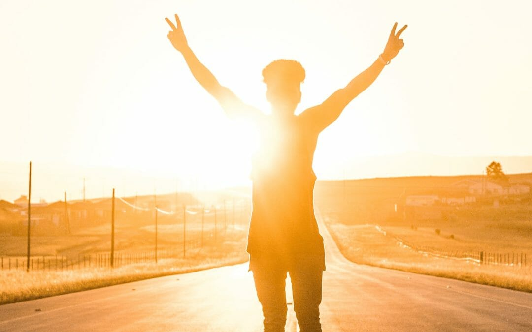 Strong year-end fundraising - image of a person in victory pose against setting sun